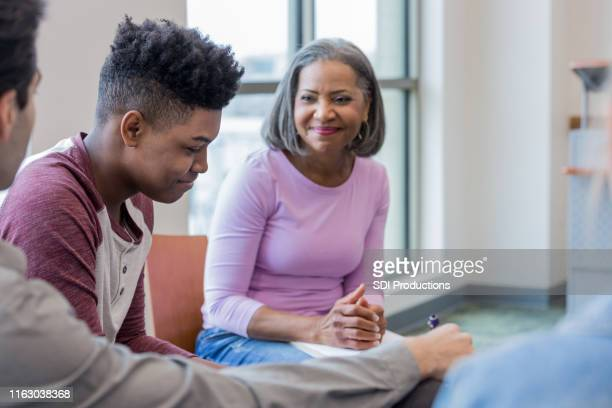 teen boy shyly looks at floor while grandmother smiles - psychotherapy stock pictures, royalty-free photos & images