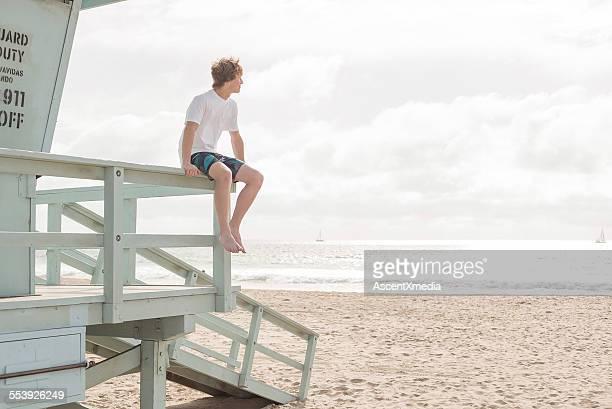 Teen boy sits on lifeguard platform, looks out