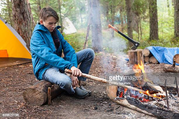 Teen boy sitting by burning campfire cooking