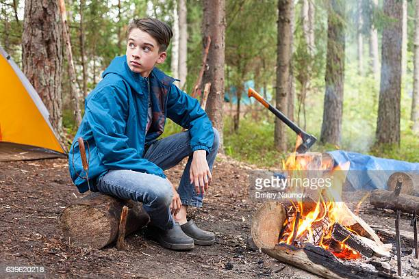 Teen boy sitting by burning campfire