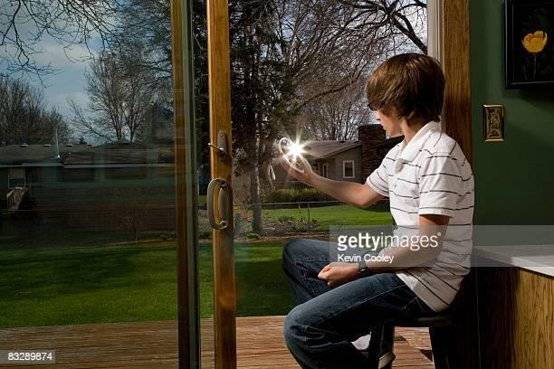 Teen boy sitting indoors, signaling with mirror