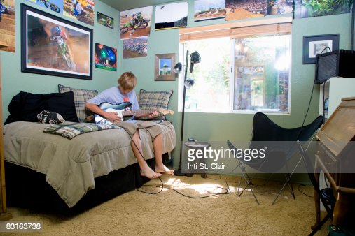 Teen Boy Sitting On Bed In Bedroom Playing Guitar Stock Photo | Getty Images