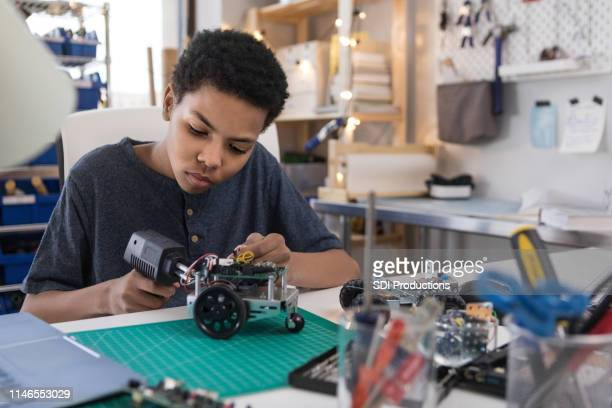 teen boy solders wires to build robot - curiosity stock pictures, royalty-free photos & images