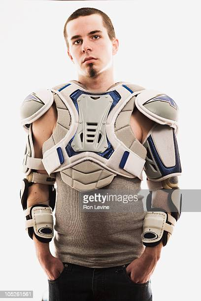 Teen boy wearing football pads, portrait