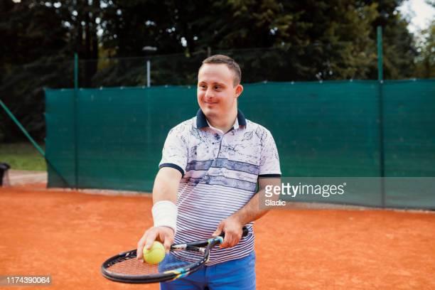 tiener jongen met down syndroom op tennisbaan - racket sport stockfoto's en -beelden