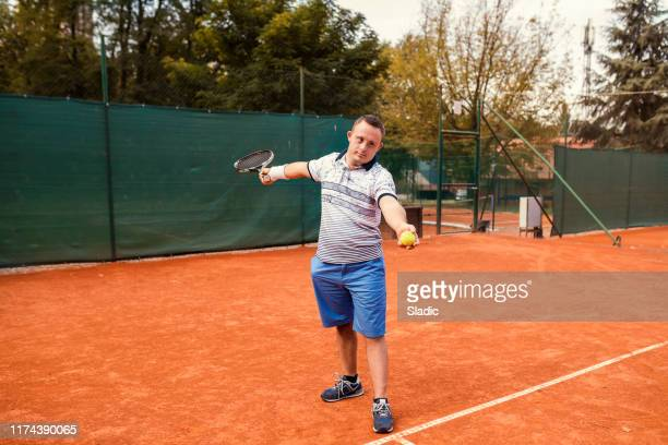 teen boy with down syndrome on tennis court - tennis racquet stock pictures, royalty-free photos & images