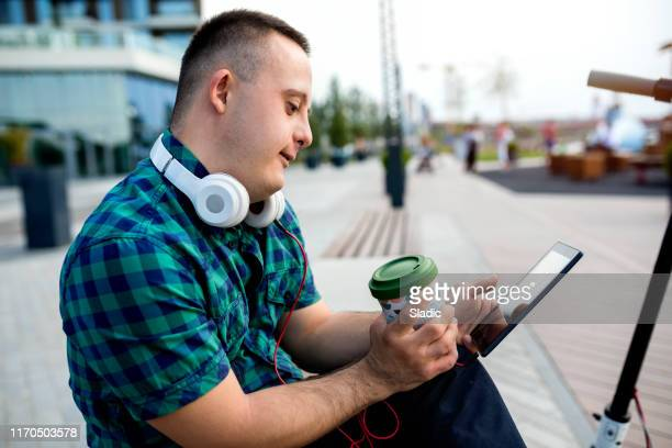 teen boy with down syndrome on the way to school - assistive technology stock photos and pictures