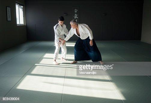 Teen boy with his sansei practicing in dojo