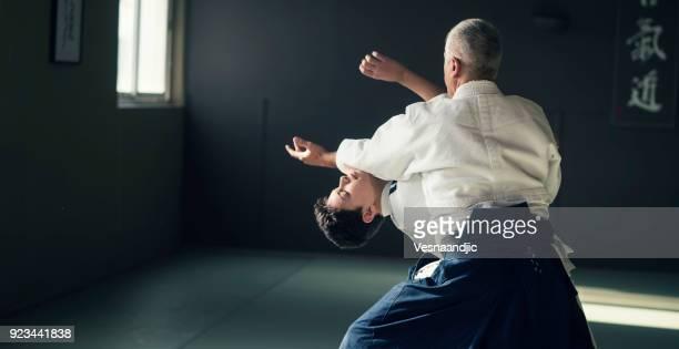 ragazzo adolescente con il suo sansei che si esercita nel dojo - difendere foto e immagini stock