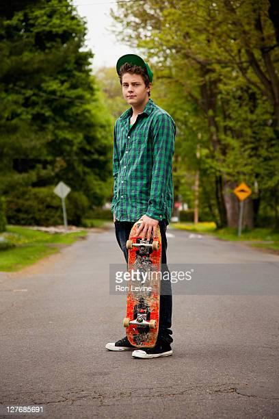 Teen boy with skateboard, portrait