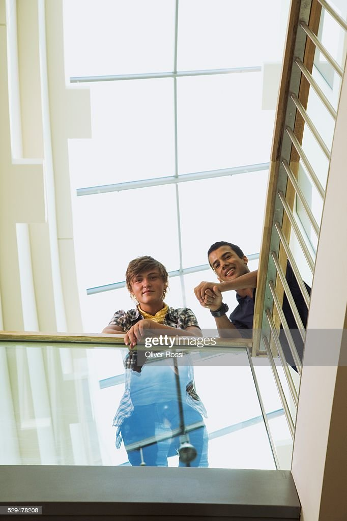 Teen boys leaning on railing : Stock Photo