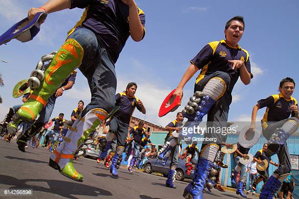 Teen boys practising Cascabeles bells formation at the Andean Carnival parade rehearsal
