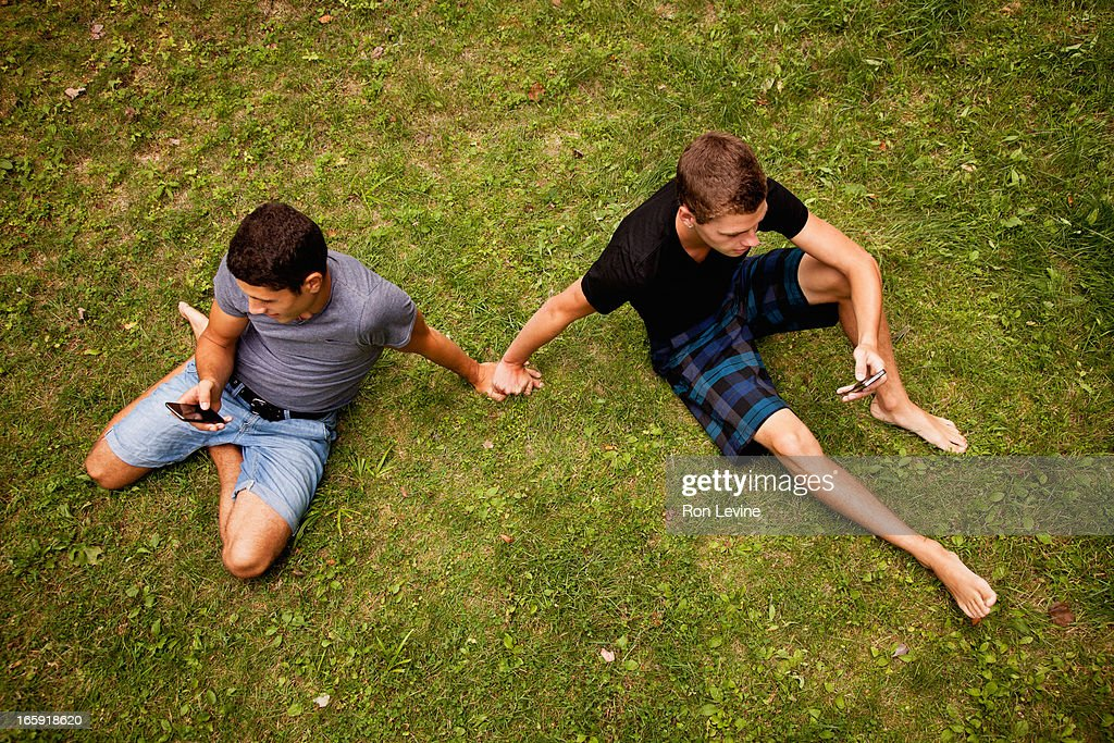 Teen Boys Using Their Cellphones Holding Hands Stock Photo  Getty Images-2073