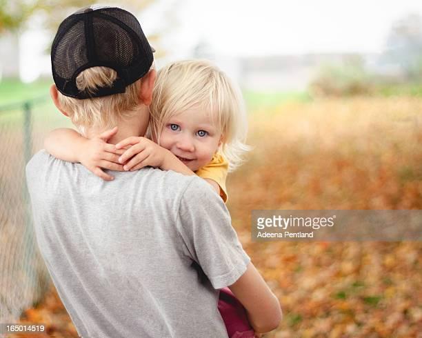 Teen carrying toddler girl