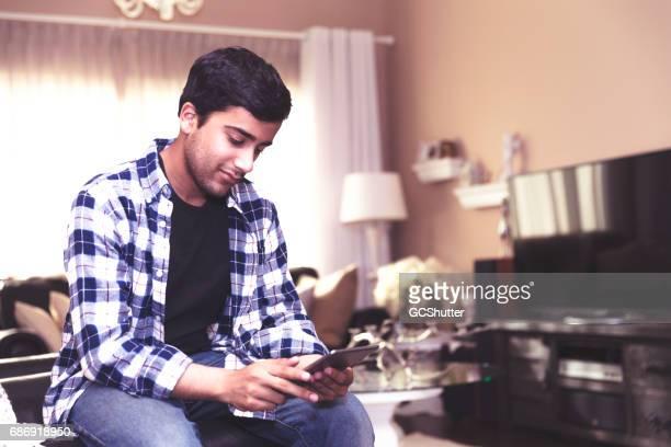 Tiener controleren zijn sociale media feed op een digitale tablet