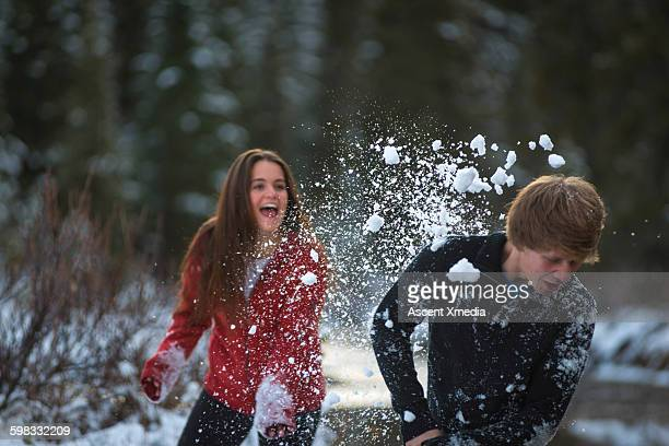 Teen couple have snowball fight in forest