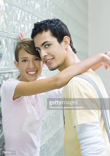 Teen couple leaning against wall