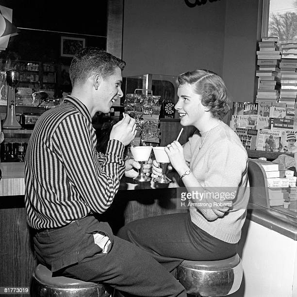 Teen Couple On Stools At Soda Fountain Drinking Shakes & Smiling At Each Other.
