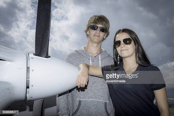 Teen couple pose in front of prop plane, airport