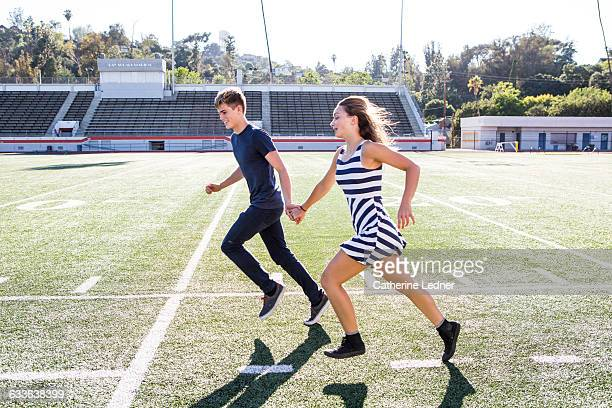 Teen couple running on football field