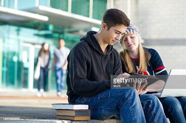teen couple studying outdoors