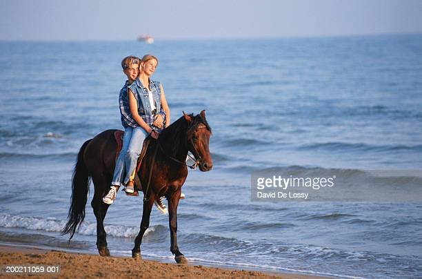 teen couple together on horseback along beach - one animal stock pictures, royalty-free photos & images
