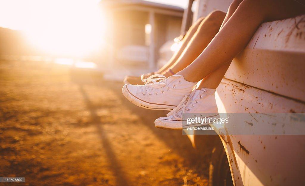 Teen paar Beine hanging out Fahrzeug mit Sonne flare : Stock-Foto