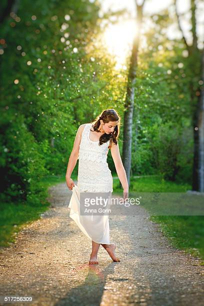 teen dancer in white on forested dirt footpath - abito senza maniche foto e immagini stock