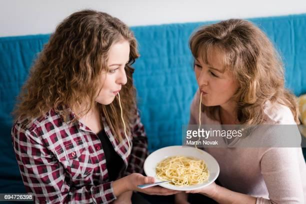 Teen daughter with he mother having fun eating pasta