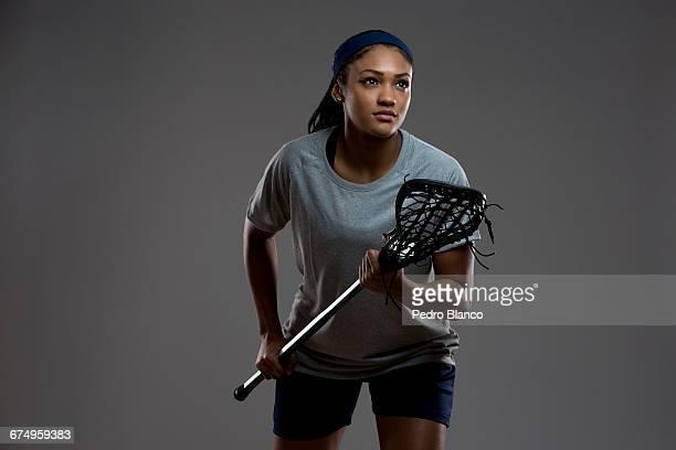 Teen female lacrosse athlete leaning stick forward