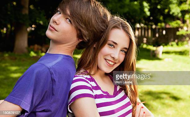 Teen fraternal twins leaning on each other