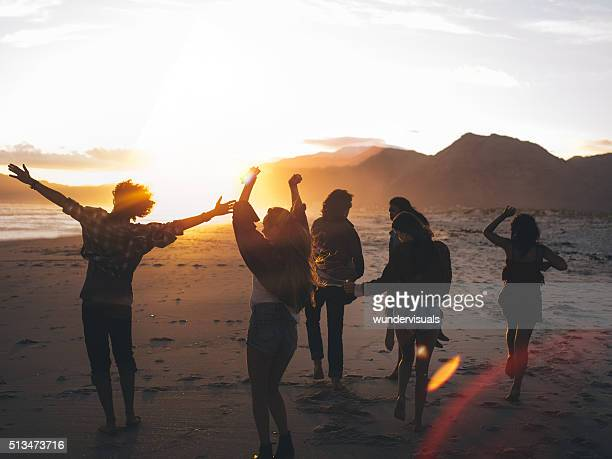 Teen friends dancing on the beach at sunset