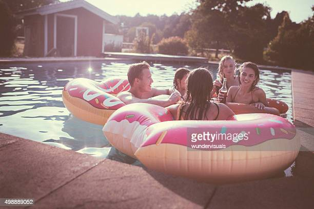 Teen friends smiling and talking in a backyard pool together