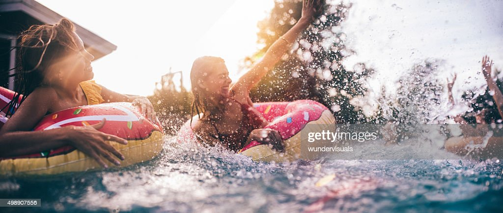 Teen friends splashing in a pool with colourful inflatables : Stock Photo