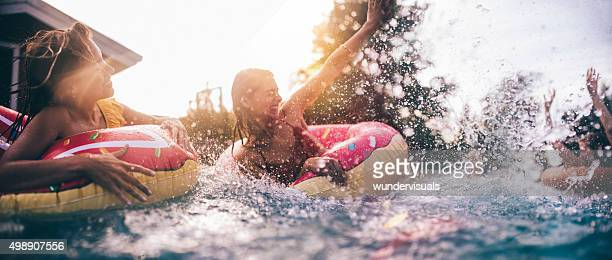 Teen friends splashing in a pool with colourful inflatables