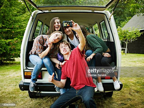 teen friends taking digital photo in rear of van - five people stock pictures, royalty-free photos & images