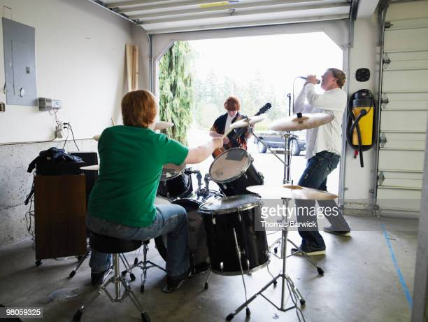 teen garage band playing rearview - garage band stock photos and pictures