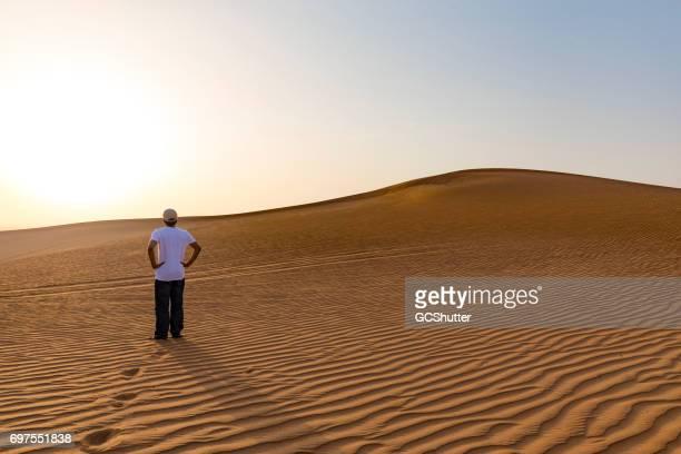 Tiener staren de horizon op de duinen of Arabia