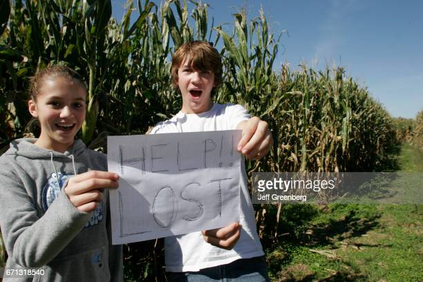 A teen girl and boy hold a help lost sign at the corn maze at Buckley Homestead