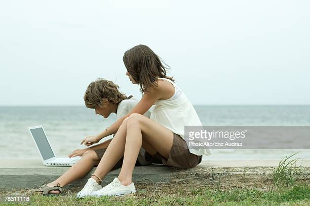 teen girl and little brother sitting on the ground, using laptop computer, one pointing and looking over the other's shoulder - looking over shoulder ストックフォトと画像