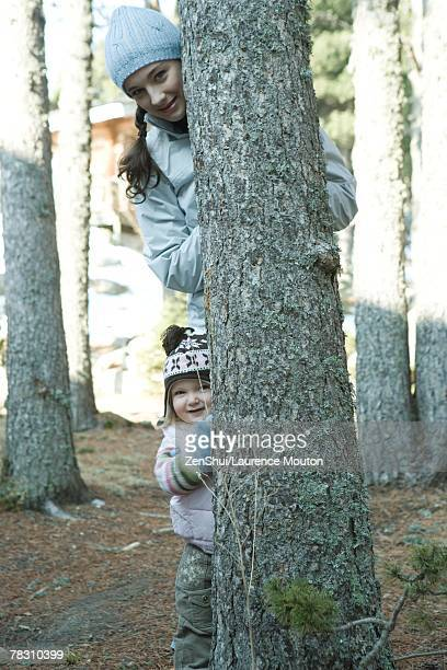 Teen girl and toddler, peeking out from behind tree trunk