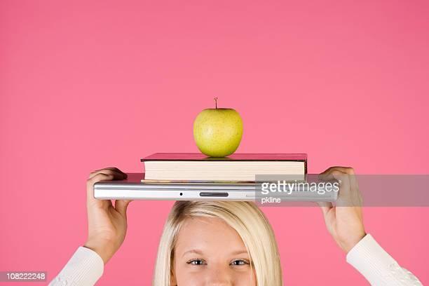 Teen girl balances school items on her head