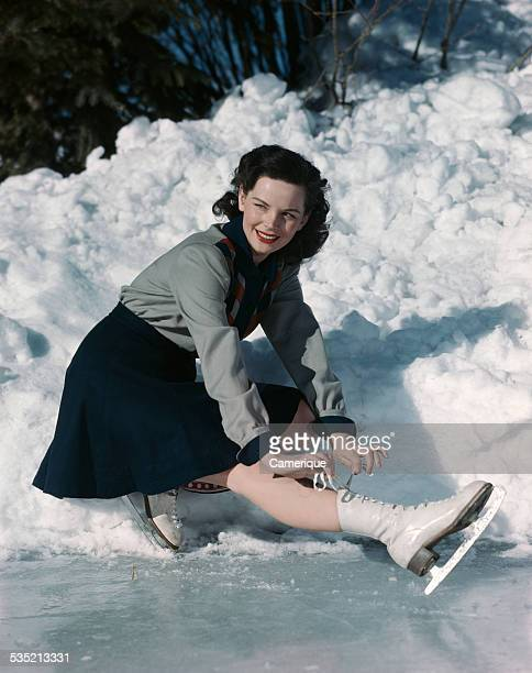 Teen girl bent over tying her ice skates Los Angeles California 1950s