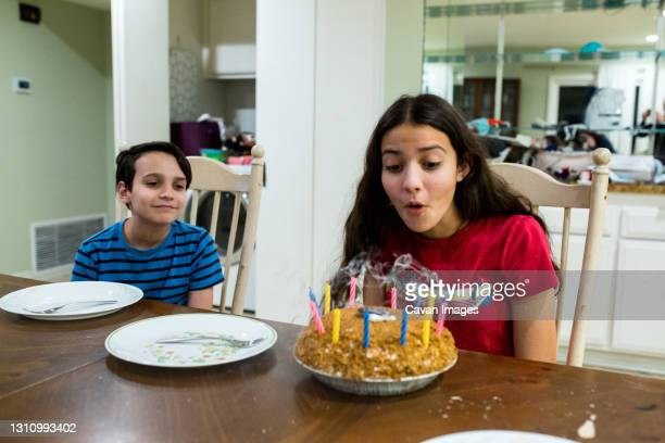 teen girl blows out candles on birthday pie - thousand oaks stock pictures, royalty-free photos & images