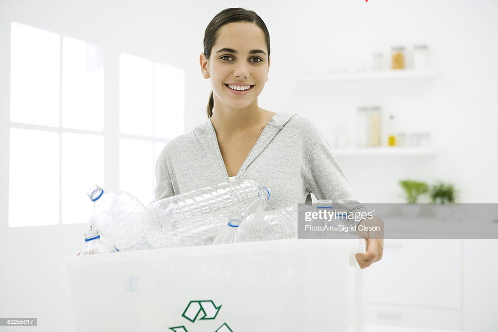 Teen girl carrying recycling bin full of plastic bottles, smiling at camera : Stock Photo