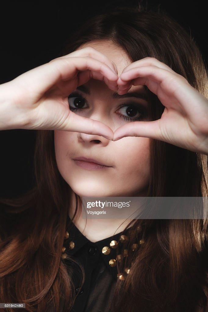 Teen Girl Doing Heart Shape Love Symbol With Hands Stock Photo