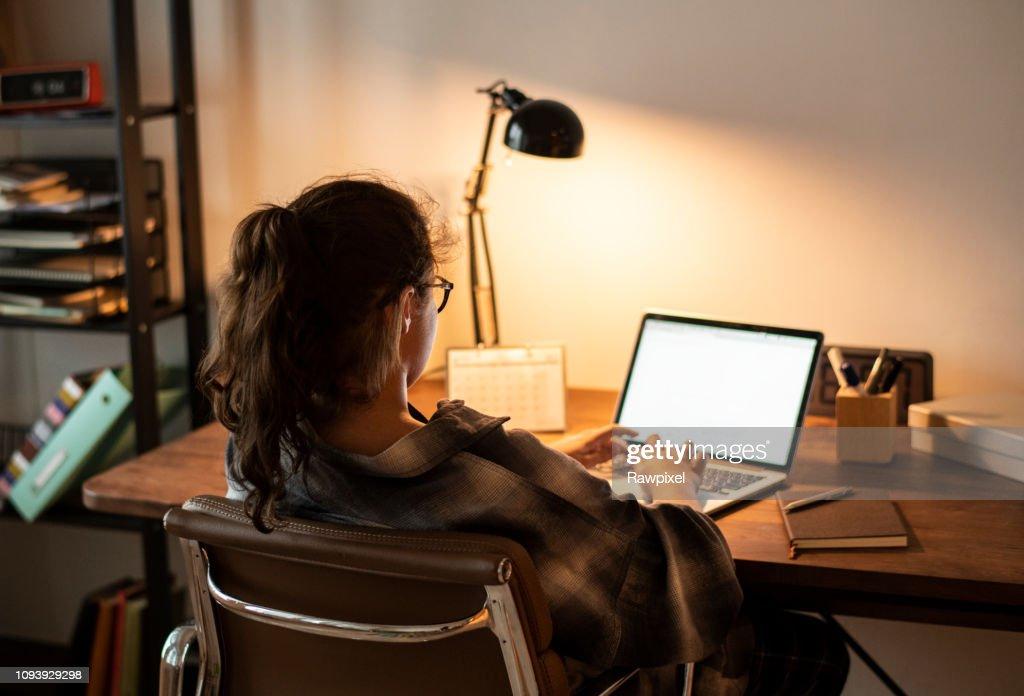 Teen girl doing homework on her laptop : Stock Photo
