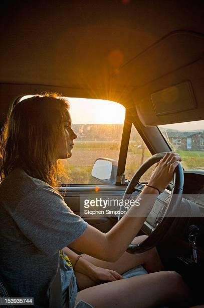 teen girl driving pickup truck at sunset