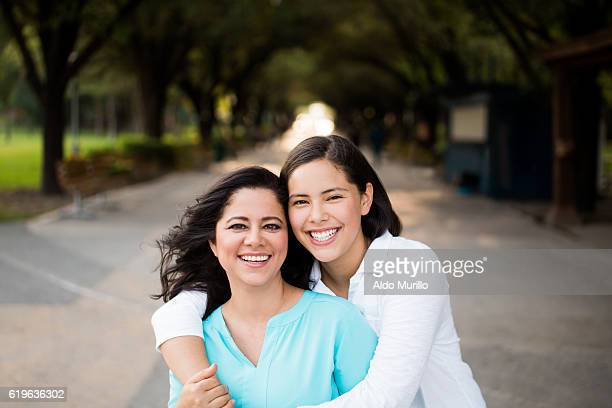 Teen girl embracing mother and smiling at camera