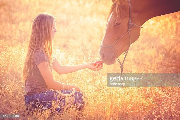 Teen girl feeding apple to horse in sunny grassy pasture